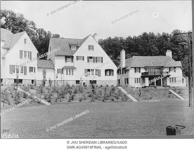 Facade of two homes on slight hill with small trees, home on right has front and second story porches with columns, field of grass in front of homes