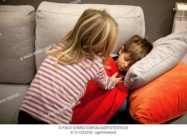 Girl tucking her brother