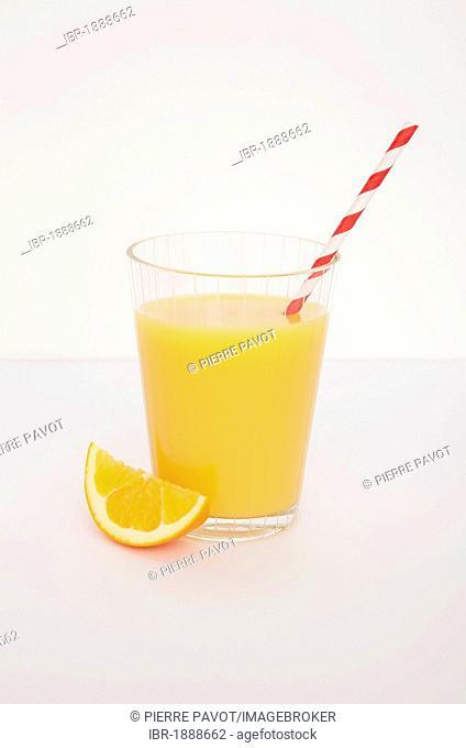 Fresh orange juice with a straw and orange