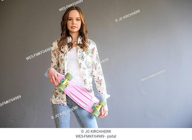 Portrait of teenage girl with pink skateboard