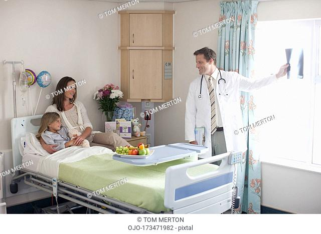 Pediatrician showing patient and mother x-ray in hospital