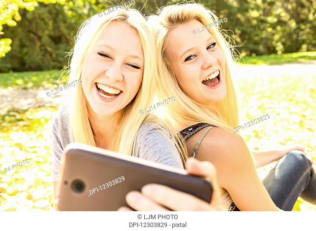 Two sisters having fun outdoors in a city park in autumn and laughing at the selfies they have taken of themselves; Edmonton, Alberta, Canada