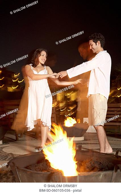 Couple dancing outdoors at night, Los Cabos, Mexico