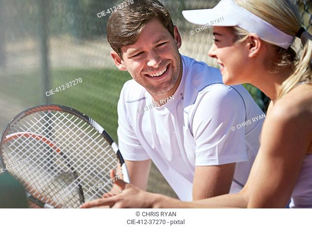 Smiling male and female tennis players resting and talking with tennis rackets in sunny outdoors
