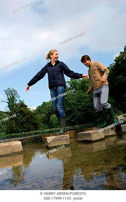 Low angle view of a young couple walking on stepping stones