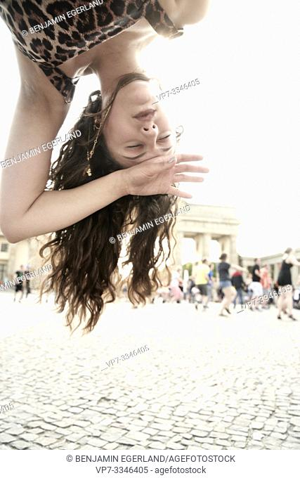 young woman upside down in front of dancing flashmob crowd at Brandenburger Tor, Brandenburg Gate, in city Berlin, Germany