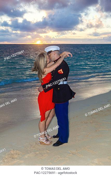 Marine and his lady getting engaged on the beach; Kailua, Island of Hawaii, Hawaii, United States of America