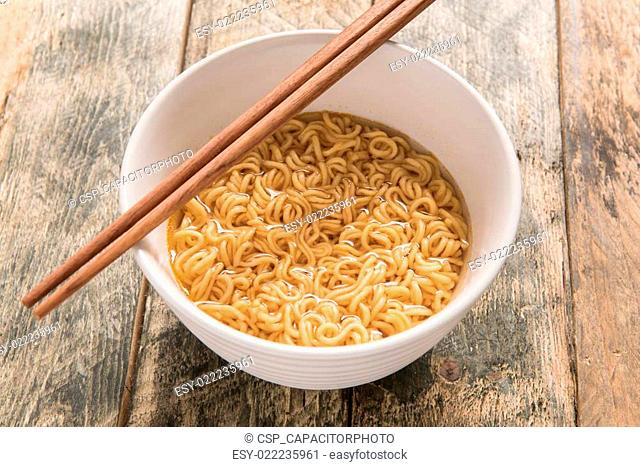 noodles in white dish on wooden background