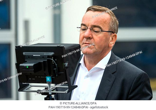 10 July 2019, Lower Saxony, Buchholz: Boris Pistorius (SPD), Minister of the Interior of Lower Saxony, looks at a press event on a screen that receives pictures...