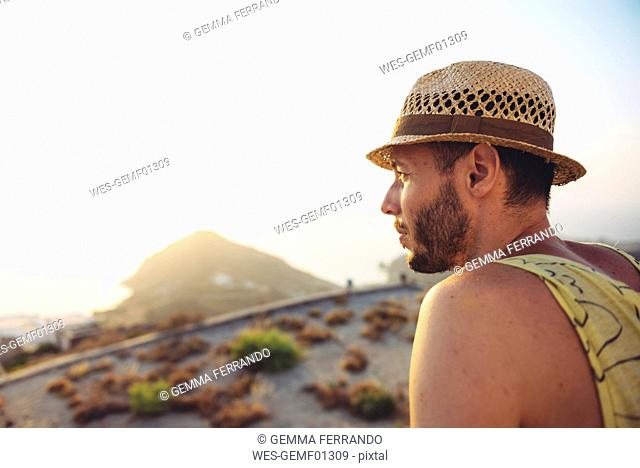 Greece, Milos, Man with straw hat looking at distance