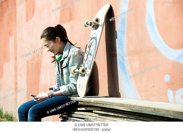 Teenage girl with skateboard using smartphone