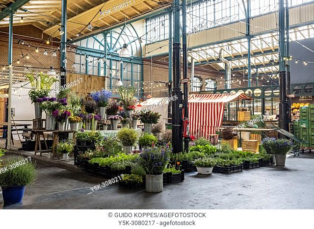 Berlin, Germany. Local markethall interior and interior decoration. One of the many stalls and entrepreneurs sells plants and flowers to neighborhood residents