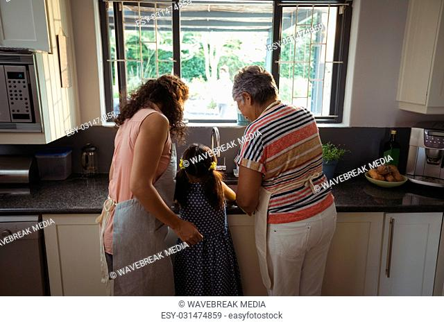 Little girl assisting mother and grandmother to wash utensil in kitchen