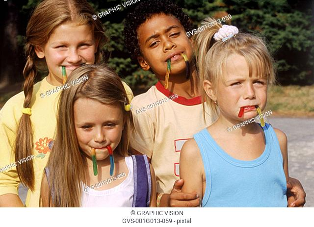 Group of young children with candy in their mouth