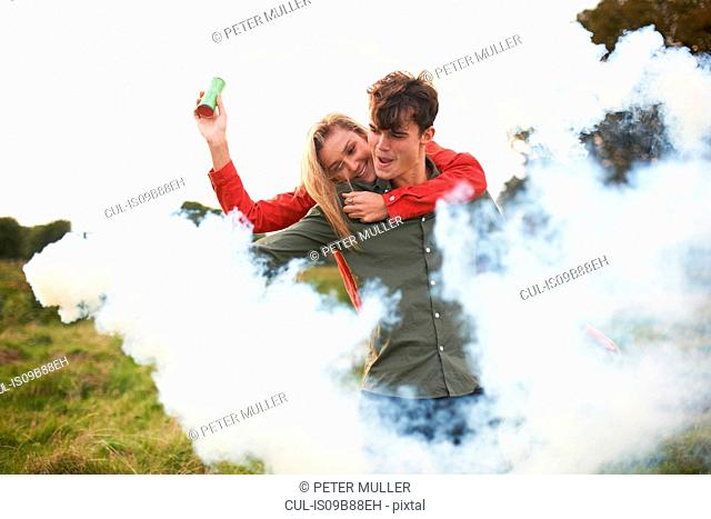 Young couple surrounded by smoke from smoke flares in field