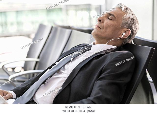 Relaxed businessman with earbuds at the airport
