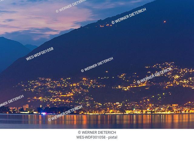 Switzerland, Ticino, View of Locarno at night with Lake Maggiore