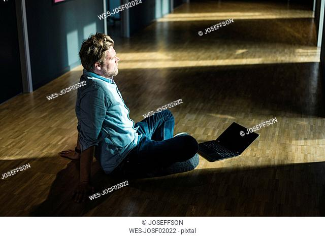 Businessman with laptop sitting on the floor in office