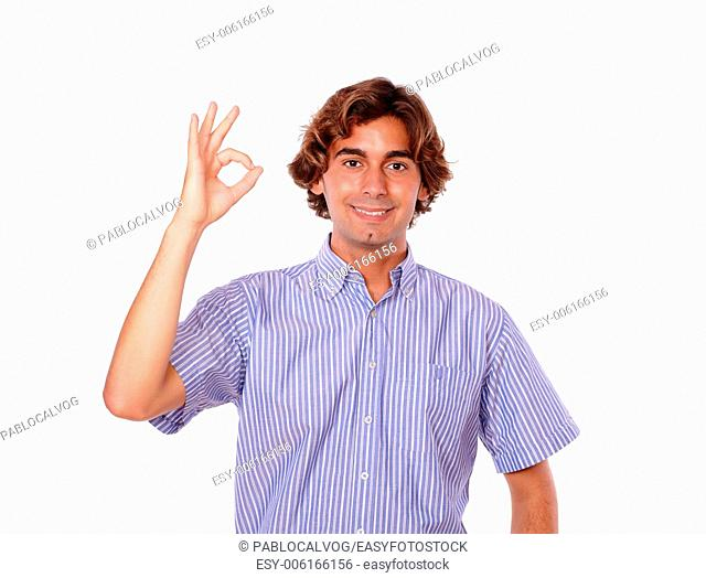 Portrait of a handsome young man smiling and showing people ok sign while is standing over white background