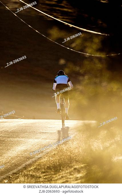 Uphill cycling in early morning, Los Altos Hills, California, USA