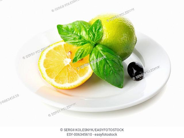 Citrus fruits with mint and olive in plate isolated on white