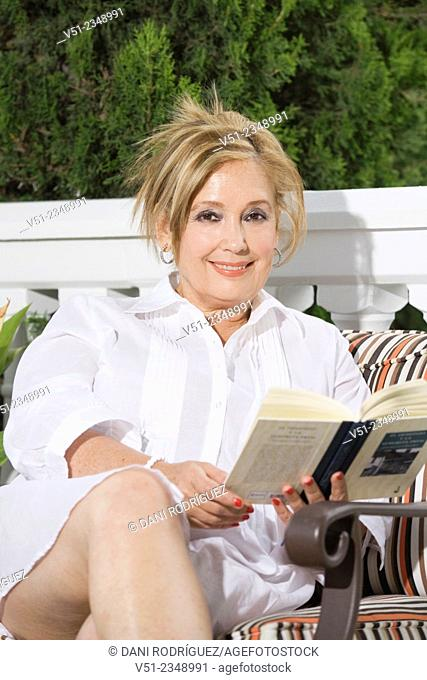 Senior woman reading a book in garden outdoors and smiling at camera