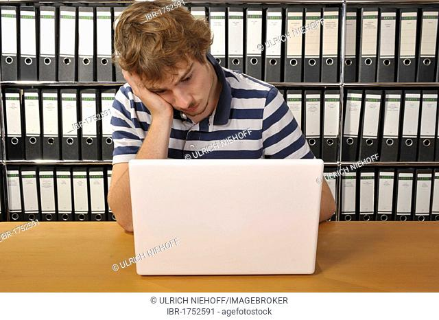 Stressed young man sitting at a desk with a notebook