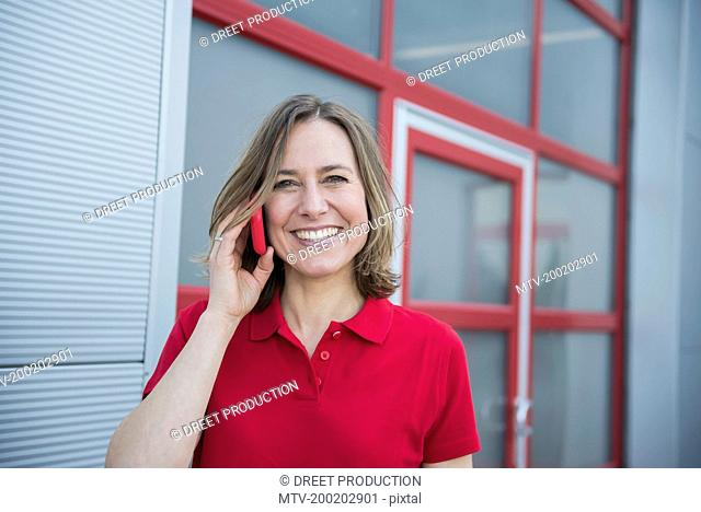 Businesswoman talking on smart phone, smiling