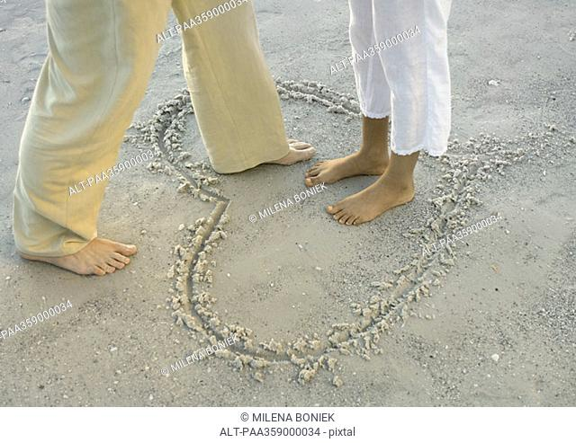Woman standing in heart drawn in sand, man stepping into heart, view of knee down