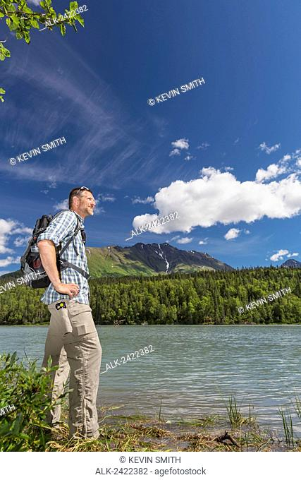 Male hiker taking in the view at a Trail lake with Kenai Mountains in the background, Summer, Moose Pass, Kenai Peninsula, Southcentral Alaska, USA