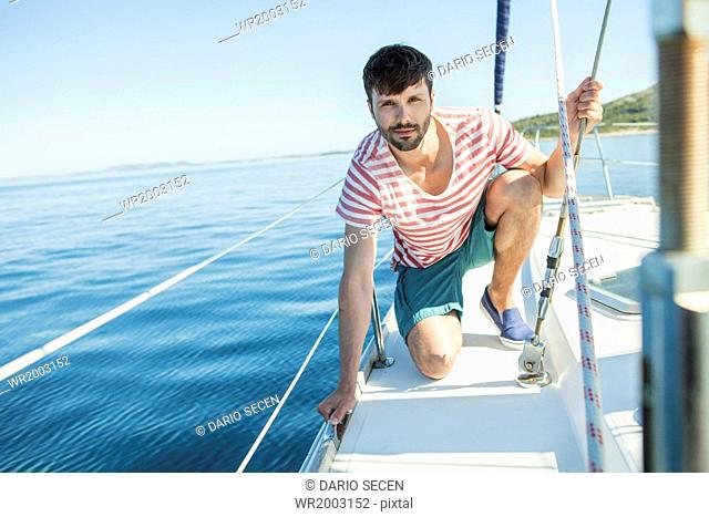 Man adjusting rigging on sailboat, Adriatic Sea