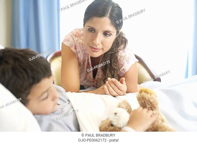Young boy sleeping in hospital bed with teddy bear and woman looking over him