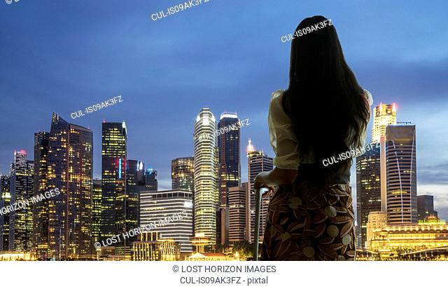 Young woman with suitcase looking at city skyline