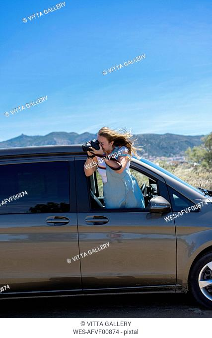 Happy woman leaning out of car window, taking pictures