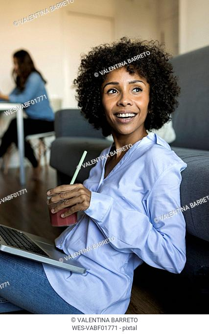 Happy woman with soft drink sitting on floor using laptop