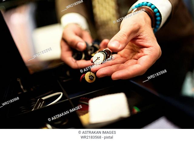 Close-up of fashion designer choosing buttons in drawer