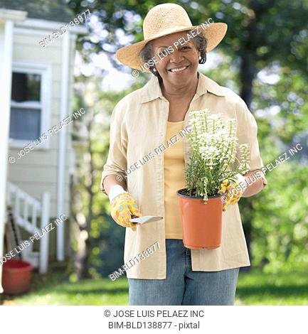 Older African American woman holding potted plant in backyard
