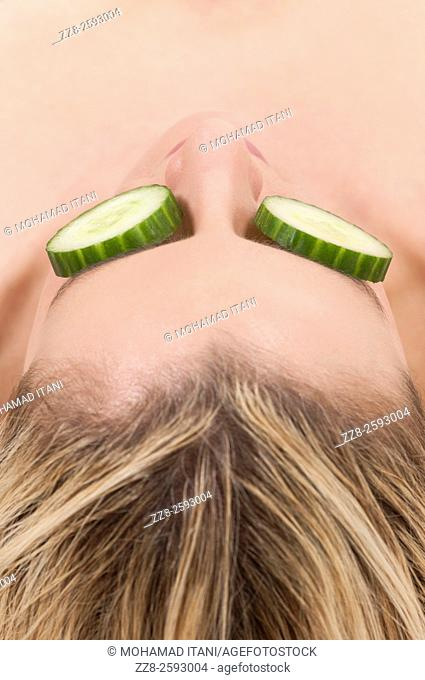Woman with slices of cumbers covering her eyes