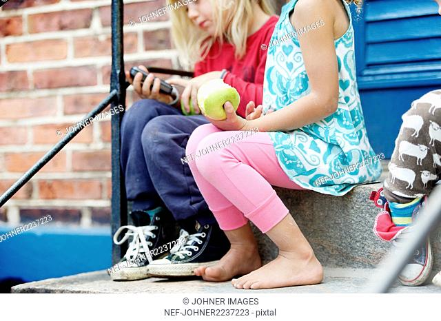 Children sitting on steps and eating apples
