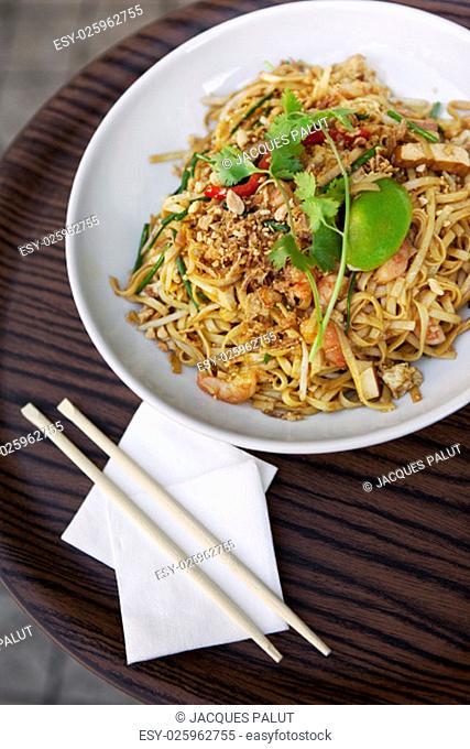 Asian noodles, pork, shrimp and eggplant on a plate