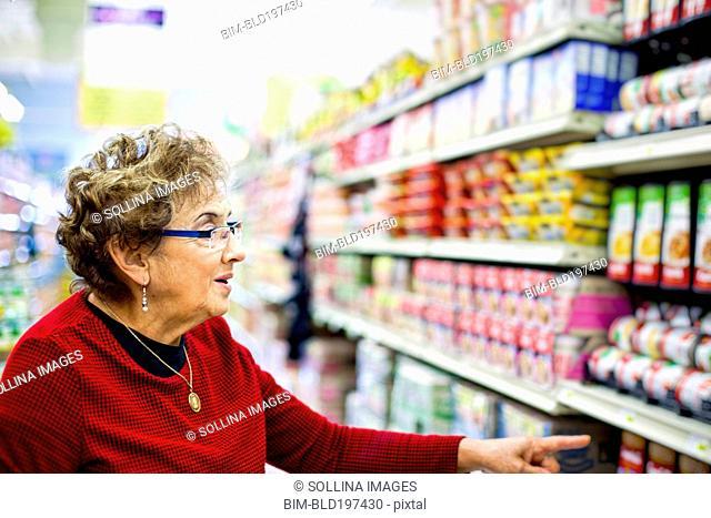 Senior Hispanic woman shopping in grocery store