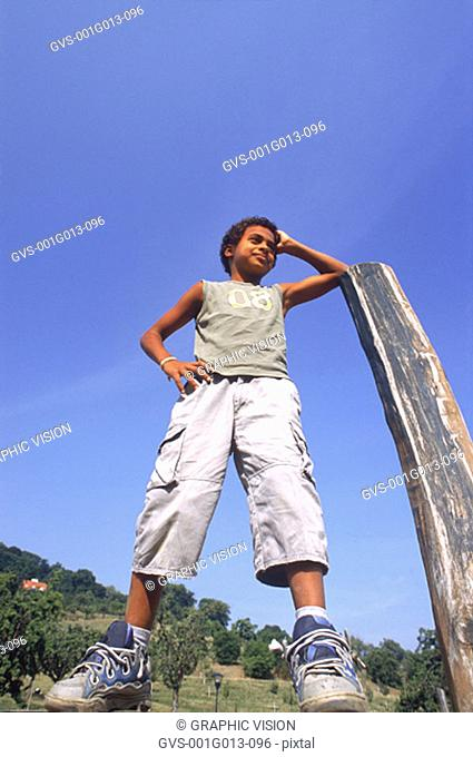 Boy leaning on a pole with a hand on his waist