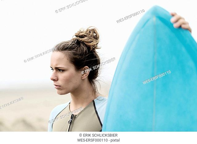 Young female surfer with surfboard