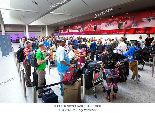 Long queue of passengers waitint to check in at Virgin Atlantic desks