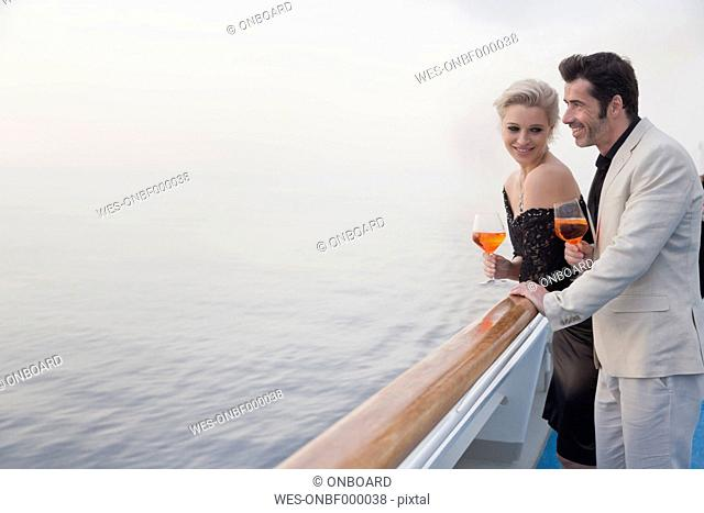 Couple with aperitive leaning on railing of a cruise liner