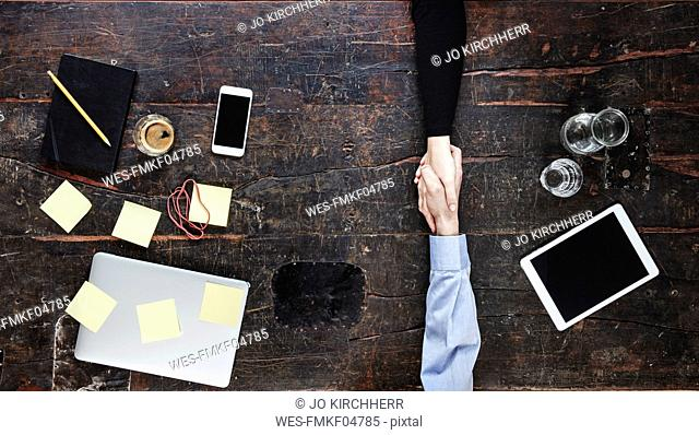 Business partners shaking hands, top view
