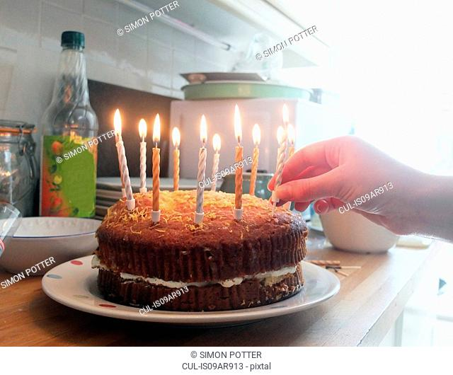 Hand of young woman placing lit candles on birthday cake
