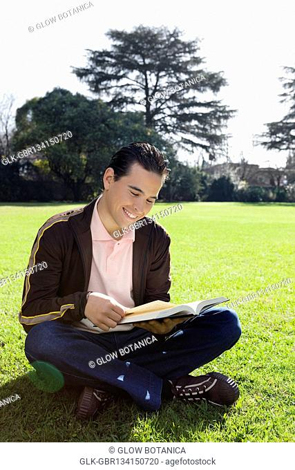 Man reading a book in a park