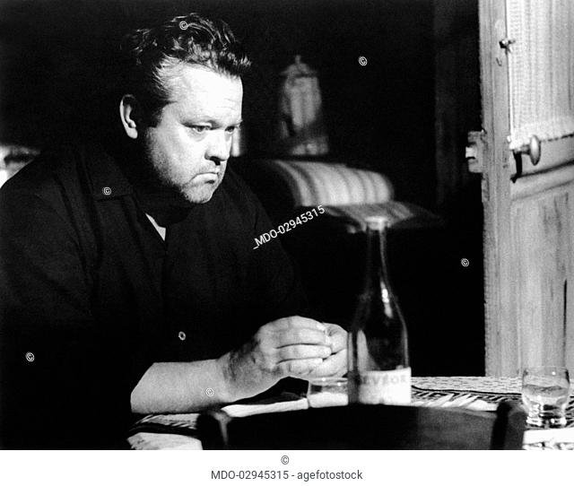American actor and director Orson Welles sitting at a table in a pensive attitude in the film Crack in the Mirror. 1960