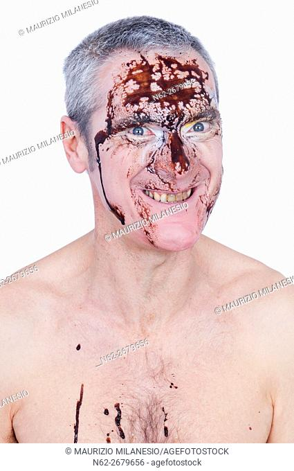 Portrait of a possessed man with a brown liquid dripping on his face, he is shirtless